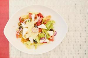 vegetarischer Salat in der Keramikplatte auf weißem Basttisch foto