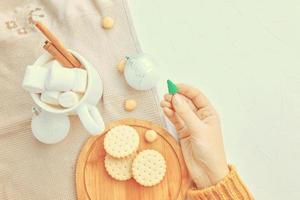 Frauen hält Weihnachtsspielzeug Tasse Kaffeeplätzchen und Tischdecke auf dem Tisch foto
