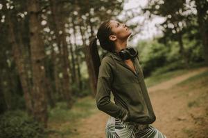 junge schöne Läuferin, die Musik hört und eine Pause macht, nachdem sie in einem Wald joggt foto