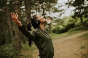 junge Frau mit Kopfhörern, die ihre Arme im Wald ausbreiten, weil sie gerne draußen trainiert foto