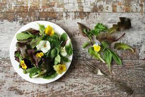 Salatmischung mit Blumen auf einem weißen Teller foto