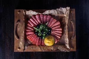 Wurst geschnitten mit Kräutern und Soße auf einem Holztablett, schöne Portion, dunkler Hintergrund foto
