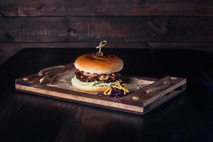 Cheeseburger auf einem Holztablett in einem Restaurant, auf dunklem Hintergrund foto