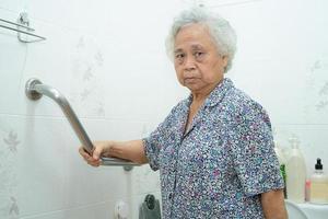 asiatische ältere oder ältere alte Dame Frau Patient verwenden Hang Gehweg Griff Sicherheit mit Hilfe Unterstützung Assistent in der Krankenstation foto
