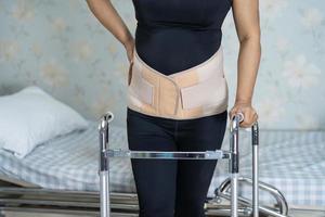 asiatische Patientin mit Rückenschmerzen Stützgürtel für orthopädische Lendenwirbelsäule mit Gehhilfe foto