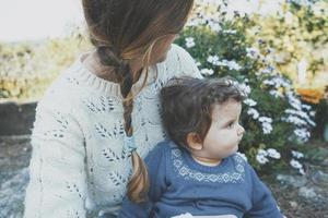 junge Mutter umarmt ihr Baby und genießt einen Frühlingstag im Garten foto