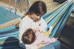 junge Frau kümmert sich um ihr Baby, das auf einer Hängematte sitzt foto