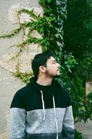 ein junger attraktiver mann in ruhiger stellung mit geschlossenen augen den kopf und draußenpflanzen hinter ihm foto