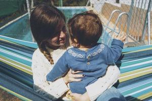 Bild über echte Mutterschaft einer jungen Mutter, die ihr Baby umarmt foto