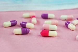 ein detailliertes Makro von Pillen und Kapseln durch eine medizinische Maske mit rosa Hintergrund foto
