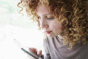 Nahaufnahmeporträt einer schönen und jungen Frau mit blauen Augen und lockigen blonden Haaren schaut auf das Smartphone, während sie auf einer Reise ist foto