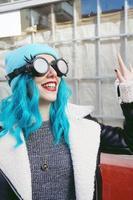 Porträt einer jungen Punk- oder Gothic-Frau lächelt mit blau gefärbten Haaren und trägt eine schwarze Steampunk-Brille und eine blaue Wollmütze in einer städtischen Straße im Freien foto