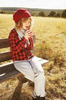 eine junge Frau in rotem kariertem Hemd mit Wollmütze und Schal, die eine Tasse Tee oder Kaffee nimmt, während sie auf einer Holzbank in einem gelben Feld mit Hintergrundbeleuchtung von der Herbstsonne sitzt foto