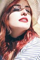Rothaariges Model schützt sich im Sommer mit einem Hut vor der Sonne foto