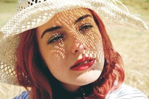 junge rothaarige Frau, die sich vor der Sonne bedeckt foto