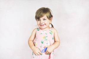 junges kleines und lustiges Mädchen in einer Studioaufnahme foto