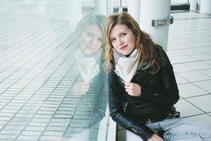 junge schöne Frau spiegelte sich in einem riesigen Fenster foto