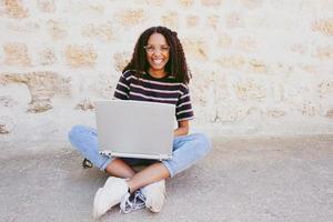 ein Porträt einer glücklich lächelnden jungen schwarzen Frau mit lockigem Haar, die eine Brille, Jeans und ein gestreiftes T-Shirt trägt, auf dem Boden sitzt und arbeitet oder Hausaufgaben macht foto