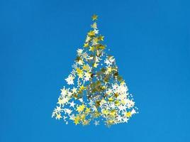 Weihnachtsbaumform aus goldenen Konfettisternen auf blauem Papier. foto