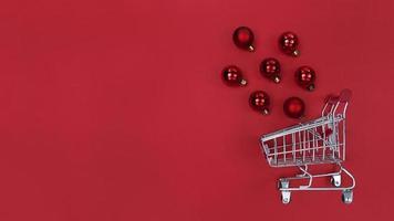 Einkaufswagen und Weihnachtsbaumkugeln auf rotem Papier. foto