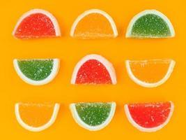 Mehrfarbige Marmelade Zitrusscheiben in Zucker auf orangem Hintergrund. foto