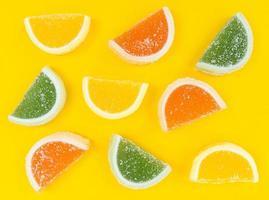 Mehrfarbige Marmelade-Zitrusscheiben in Zucker auf gelbem Hintergrund. foto