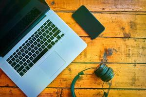 Flache Lage von Laptop, drahtlosen Kopfhörern und Mobiltelefonen auf Holztisch. foto