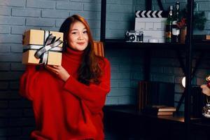 asiatisches Mädchen mit Geschenk in ihren Händen. foto