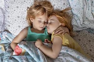 zwei kleine Geschwister Mädchen Schwestern schlafen in einer Umarmung im Bett unter einer Decke foto