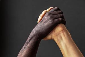 Schwarze und weiße männliche Hände. Das Konzept der Gleichheit und der Kampf gegen Rassismus. foto