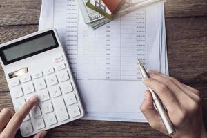 Kunden verwenden Stifte und Taschenrechner, um Wohnungsbaukredite anhand der von der Bank erhaltenen Kreditunterlagen zu berechnen foto
