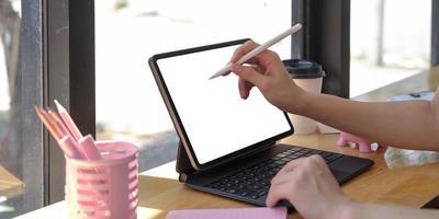 Nahaufnahme einer Frau, die ein digitales Tablet-Gerät der neuen Version mit einem intelligenten Bleistift in den Händen hält foto