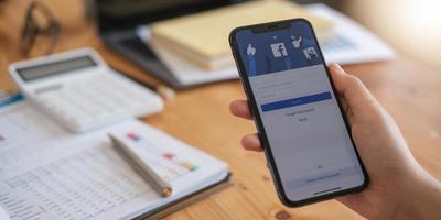 chiang mai, thailand 18. august 2020 - frau, die ein iphone x mit sozialem internetdienst facebook auf dem bildschirm hält. foto