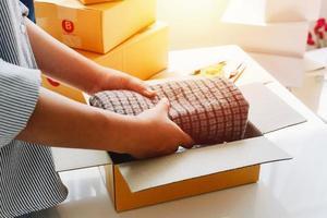 Detailansicht des Online-Shops der Frau, Verkäufer von Kleinunternehmern, Verpackungspaket für Unternehmer, Postversandkarton, der Lieferpakete auf dem Tisch vorbereitet, unternehmerisches selbstständiges Geschäftskonzept foto