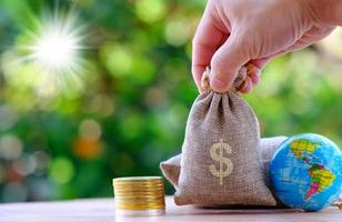 Hand, die einen Geldbeutel mit Münzen und einem Globus auf einem Bokeh-Naturhintergrund hält foto