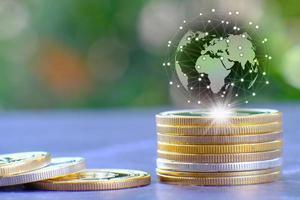 eine Abbildung eines Globus auf einem Stapel Münzen foto