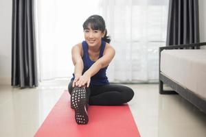 schöne junge sportliche Frau, die sich zu Hause ausdehnt foto