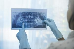 Zahnärztin, die ein Zahnröntgen hält foto