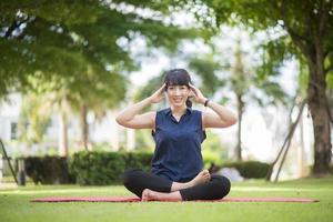 schöne Yoga-Frau auf grünem Park foto
