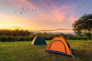 reisen, um das Zelt am Abend auf einer weiten, offenen Fläche auszubreiten. der goldene himmel bergblick auf den nakhasat sabai in chiang mai thailand foto