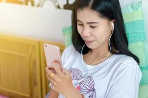 Frau, die Telefon auf dem Bett spielt, Kopfhörer aufsetzt und Musik hört. Asiatin foto