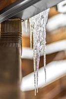 ein großer durchsichtiger Eiszapfen hängt vom Dach des Hauses. Winterfrost foto