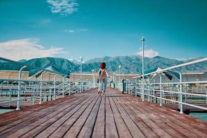 Rothaariges Mädchen läuft am Pier entlang. foto