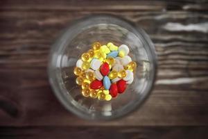 Flaches Glas mit bunten Vitaminen und Pillen im Inneren. foto