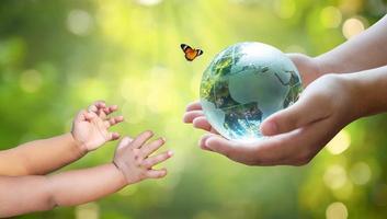 Erwachsene schicken Babys die Welt. Konzepttag Erde rette die Welt rette die Umwelt Die Welt liegt im Gras des grünen Bokeh-Hintergrunds foto