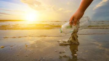 die Hand sammelt Müll am Strand auf, die Idee des Umweltschutzes foto