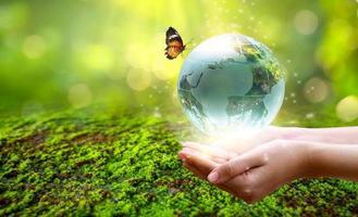 ein mann mit einem glaskugelkonzept tag erde rette die welt rette die umwelt die welt ist im gras des grünen bokeh-hintergrundes foto