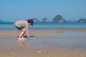junge asiatische frau, die gebrauchte plastikflaschen vom strand sammelt, um die umwelt und das meeresökosystem zu retten foto