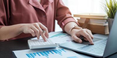 Frau mit Finanzbericht und Taschenrechner. Frau mit Taschenrechner, um Bericht am Tisch im Büro zu berechnen calculate foto