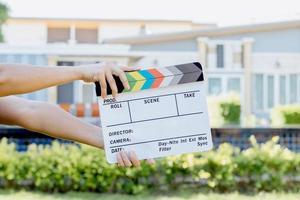 Hand, die Filmschieferfarbentafel für Filmkino und Fernsehindustrie auf grünem Hintergrund hält foto